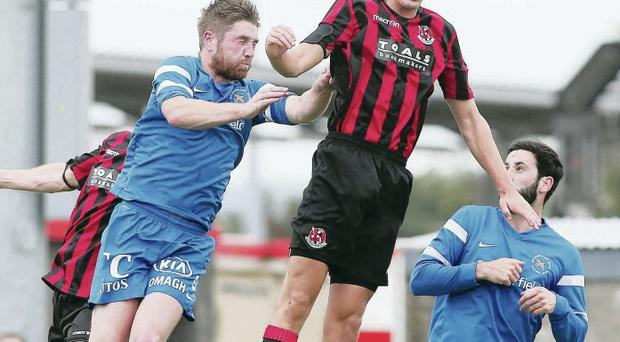 Heads up: Crusaders' two-goal hero Joshua Robinson contests an aerial tussle with Mallards skipper Mark Stafford