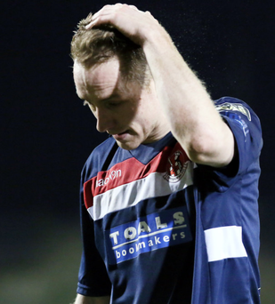 Dejected: Crusader's Timmy Adamson walks off the pitch at Shamrock Park