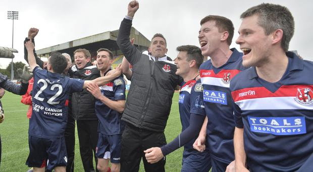 Just champion: Crusaders boss Stephen Baxter and his players celebrate title glory after Saturday's win at Cliftonville