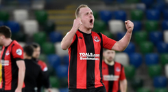 Cup hero: Jordan Owens roars with delight after helping Crusaders through courtesy of a rasping drive that gave Linfield goalkeeper Gareth Deane no chance