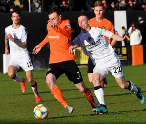Crunch time: Carrick ace Lee Chapman gets away from Paul Heatley of Crusaders
