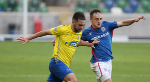 Hands on: Chris Hegarty keeps a close watch on Linfield's two-goal star Joel Cooper
