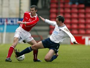 Flashback: Cliftonville defender Mickey Donnelly cuts back inside this challenge from Ards striker David Rainey