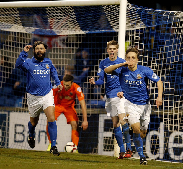 Net gains: Joel Cooper wheels away with Gary Hamilton and Rhys Marshall after hitting Glenavon's winner