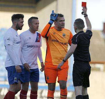 Referee Tim Marshall shows the red card to Roy Carroll