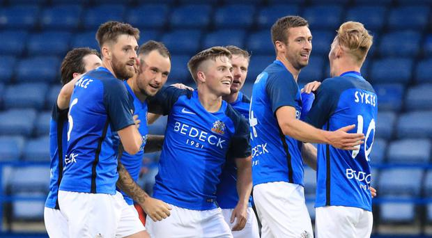 Leading man: Josh Daniels (centre) is all smiles after bagging Glenavon's winner