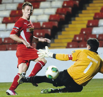 Polished finish: Cliftonville's Stephen Garrett slots the ball past Glentoran
