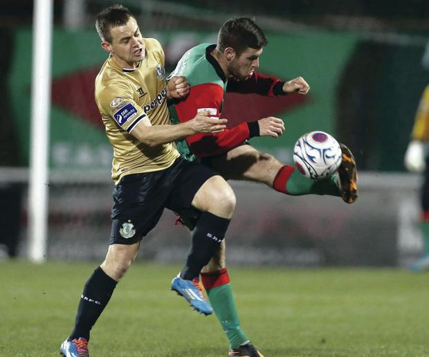 In the back: Glentoran's Mark Clarke clears under pressure from Shane Robinson of Shamrock Rovers