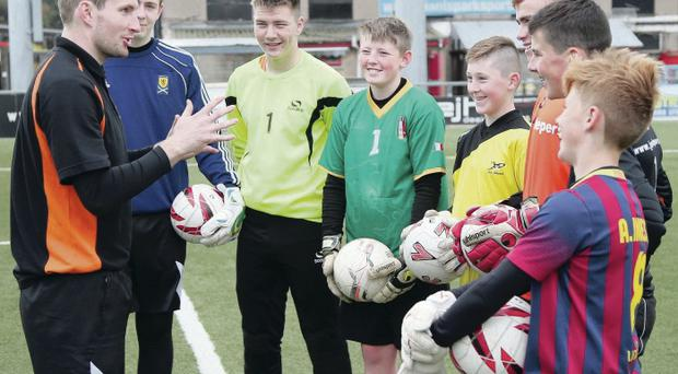 Keeping informed: Crusaders shot-stopper Sean O'Neill offers some expert advice to aspiring number ones at Seaview during this week's goalkeeping camp