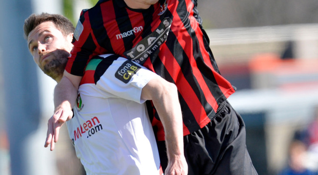 Heads up: Billy Joe Burns challenges Glentoran midfielder David Scullion in the air