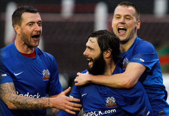 Suspended motion: Gareth McKeown and Ciaran Caldwell mob Gary Hamilton after he struck to put Glenavon ahead