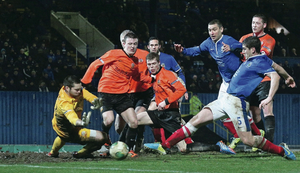 Linfield defender Mark Haughey pokes the ball home to give the Blues victory over Glenavon