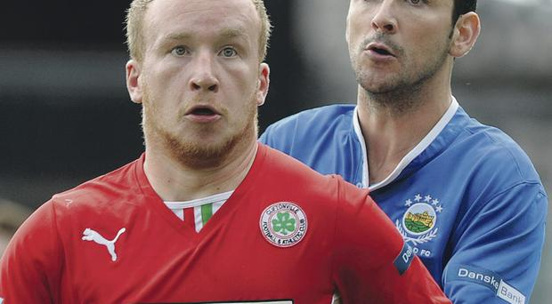 Eyes on the ball: Blues captain Michael Gault puts pressure on Cliftonville's Liam Boyce during the Danske Bank Premiership clash at Windsor Park on Saturday