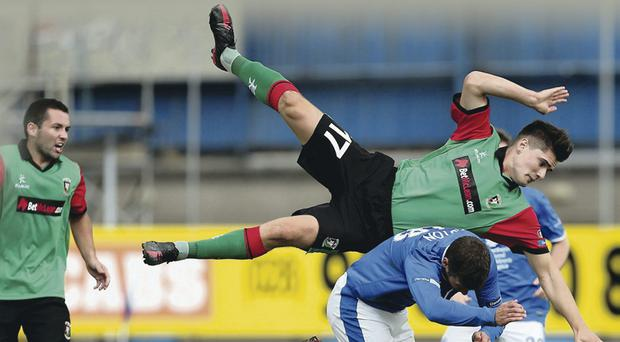 Up and away: Glentoran's Jimmy Callacher faces an awkward landing after challenging Linfield striker Matthew Tipton