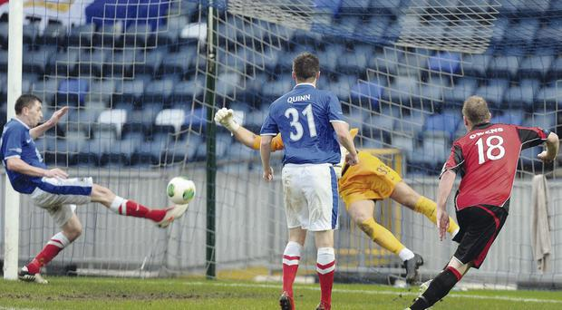 Big scare: Linfield's Billy Joe Burns makes a goal-line clearance from a Jordan Owens header