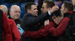 Job done: David Healy celebrates with staff at the final whistle