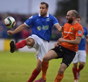 Closed down: Linfield striker Guy Bates is challenged by Carrick's Ryan Kane in the Premiership clash