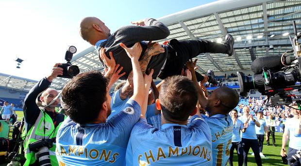 Manchester City manager Pep Guardiola is lifted up by his players after winning the title (Gareth Fuller/PA)
