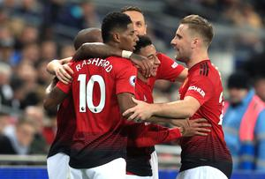 Rashford, left, is embraced by team-mates after his winner against Tottenham (Mike Egerton/PA)