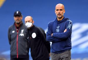 Masked fourth official Mike Dean, centre, peers past Pep Guardiola during Manchester City's thrashing of champions Liverpool. City gave Jurgen Klopp's Reds a belated reminder of their power as they thrashed their newly-crowned successors 4-0 at the Etihad Stadium in early July (Laurence Griffiths /PA)