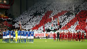 Everton and Liverpool players observe a minute's silence at Anfield (Richard Sellers/PA)