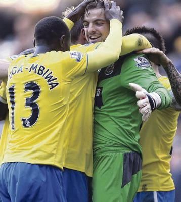 Newcastle United's goalkeeper Tim Krul is mobbed as his team mates celebrate following the Barclays Premier League match at White Hart Lane, London