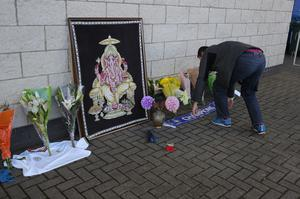 A person lays flowers outside Leicester City Football Club (Aaron Chown/PA)