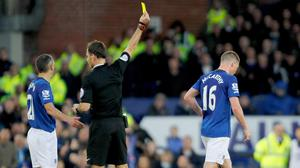 Referee Mark Clattenburg booked Everton's James McCarthy, right, after the incident