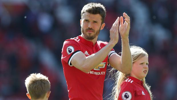 Michael Carrick applauds the fans after his final game