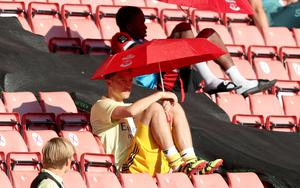 Arsenal's forgotten man Mesut Ozil shelters from the sun under a Southampton umbrella at St Mary's in June. Coronavirus restrictions resulted in substitutes being moved from dugouts and into the stands in order to comply with social-distancing rules. Germany midfielder Ozil did not play a single minute for the club post-lockdown (Andrew Matthews/PA)