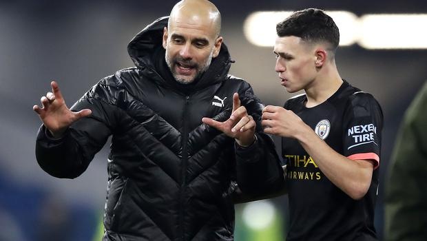 Manchester City manager Pep Guardiola celebrates the victory with Phil Foden (Martin Rickett/PA)