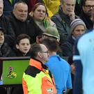 Referee Paul Tierney consults the pitchside monitor before sending off Norwich's Ben Godfrey (Joe Giddens/PA)