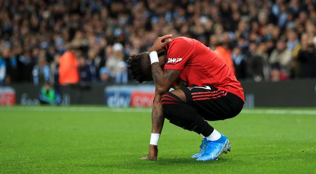 Fred crouches down after apparently being hit by objects thrown from the stands (Mike Egerton/PA)