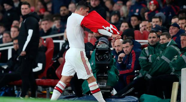 Biting back: Granit Xhaka rips off his Arsenal shirt after being booed as he was substituted