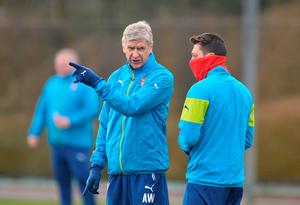 Pointing the way: Arsene Wenger gives instructions to Mesut Ozil during Arsenal's training session ahead of facing Monaco
