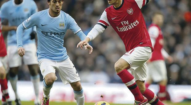 David Silva takes on Mesut Ozil