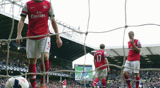 Sinking feeling: Thomas Vermaelen retrieves the ball from the back of the net as Arsenal go 3-0 down at Goodison yesterday