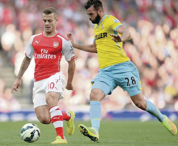 Tough tussle: Arsenal's Jack Wilshere and Crystal Palace midfielder Joe Ledley battle for the ball at the Emirates