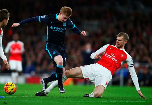 My ball: Per Mertesacker of Arsenal tackles City's Kevin de Bruyne during Monday's clash
