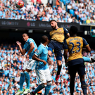 On a high: Olivier Giroud rises to head in Arsenal's first goal at the Etihad