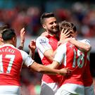 Three and easy: Olivier Giroud is congratulated by his Arsenal teammates after scoring