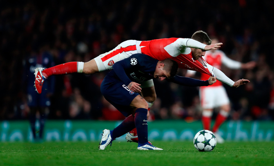 Over the top: Aaron Ramsey commits a foul on PSG's Marco Verrati