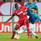 Getting shirty: Mathieu Debuchy jostles with Koln's Sehrou Guirassy at the RheinEnergieStadion
