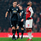 Beaten: Alexandre Lacazette shows his frustration as victorious United midfielder Nemanja Matic approaches him following the final whistle