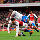 Penalty point: Mesut Ozil tumbles in a tangle with Bruno Martins Indi