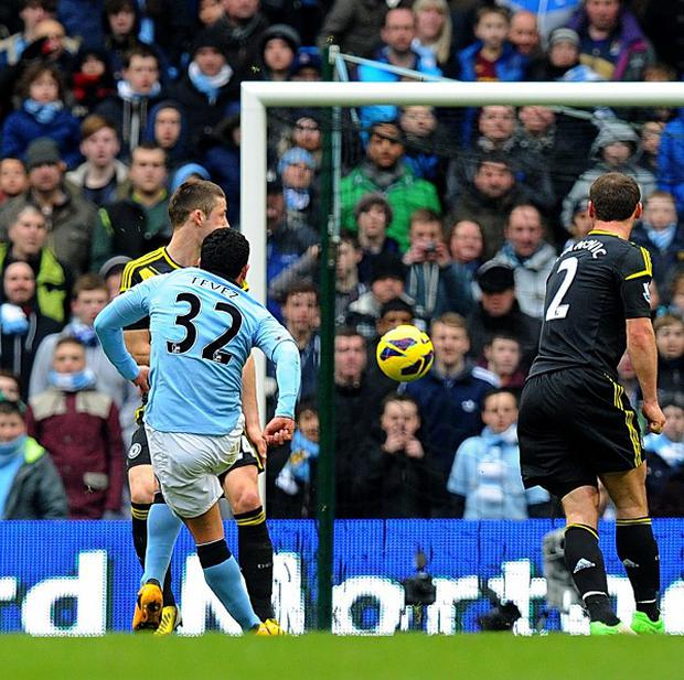 Manchester City's Carlos Tevez, left, scores his side's second goal of the game