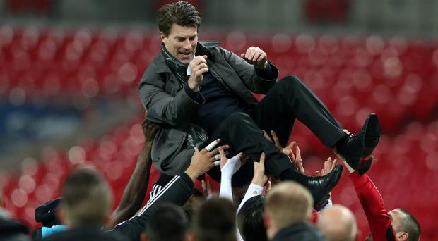 LONDON, ENGLAND - FEBRUARY 24: Swansea players lift up Manager of Swansea City Michael Laudrup after their 5-0 victory in the Capital One Cup Final match between Bradford City and Swansea City at Wembley Stadium on February 24, 2013 in London, England. (Photo by Scott Heavey/Getty Images)