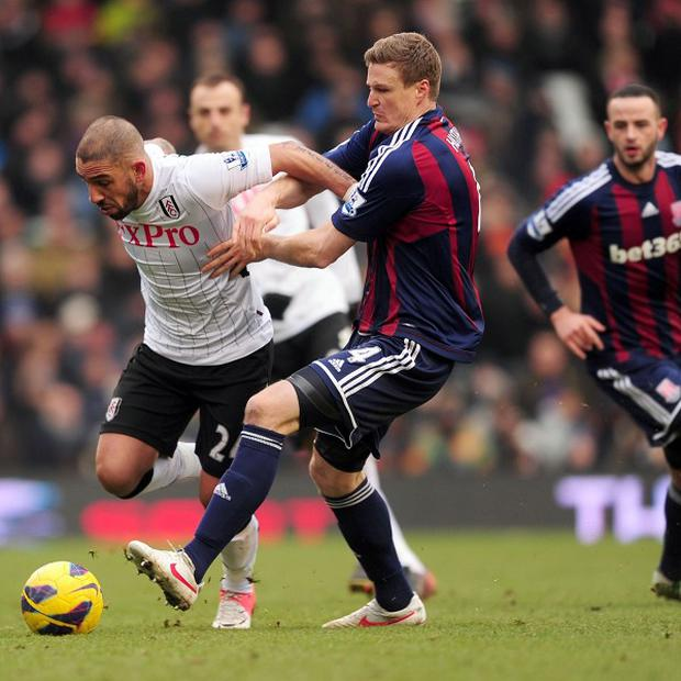 Fulham's Ashkan Dejagah, left, and Stoke Robert Huth, centre, battle for the ball
