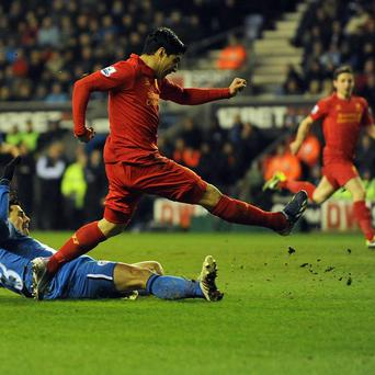 Luis Suarez, centre, completes his hat-trick with Liverpool's fourth goal against Wigan