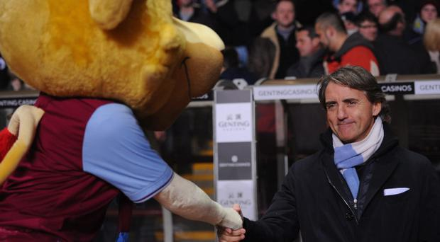 BIRMINGHAM, ENGLAND - MARCH 04: Manchester City manager Roberto Mancini shakes hands with a Villa mascot before the Barclays Premiership match between Aston Villa and Manchester City at Villa Park on March 4, 2013 in Birmingham, England. (Photo by Michael Regan/Getty Images)